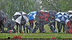 Golfers standing in the rain