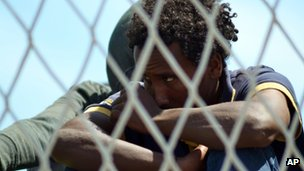 A migrant waits to disembark from the Italian Navy ship Sirio after being rescued in the Mediterranean Sea, in Augusta, Sicily (13 May 2014)