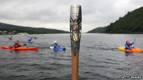 e Queen's Baton is held in front of lake Llyn Padarn at Llanberis in Wales