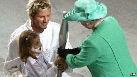 Kirsty Howard and footballer David Beckham handing the baton to the Queen