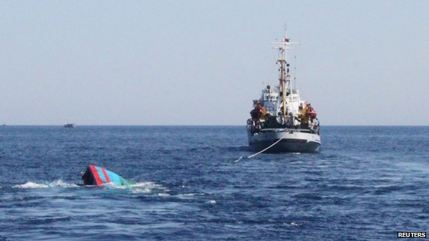 A Vietnamese boat sinking (L) after it was rammed and sunk by Chinese vessels near disputed Paracels Islands, on 29 May 2014.