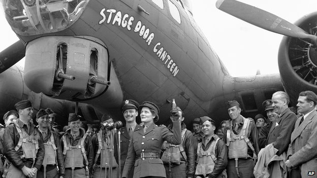 Subaltern Mary Churchill christens the new Flying Fortress, 'Stage Door Canteen', by breaking a bottle of Coca-Cola across the nose, April 23, 1944, in England. Laurence Olivier is standing at far right.