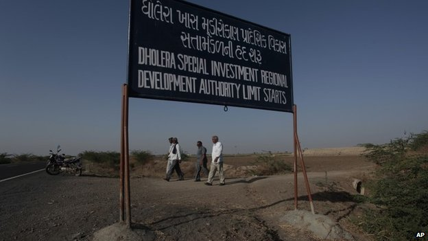 Indian farmers walk past a sign board at Bavaliari village in Dholera Special Investment Region (SIR), Gujarat, India.