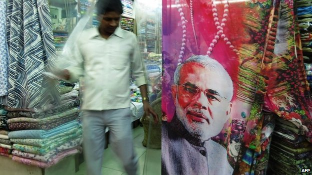 A Indian man walks past a sari, with a portrait of Indian Prime Minister Narendra Modi, displayed outside a shop in New Delhi