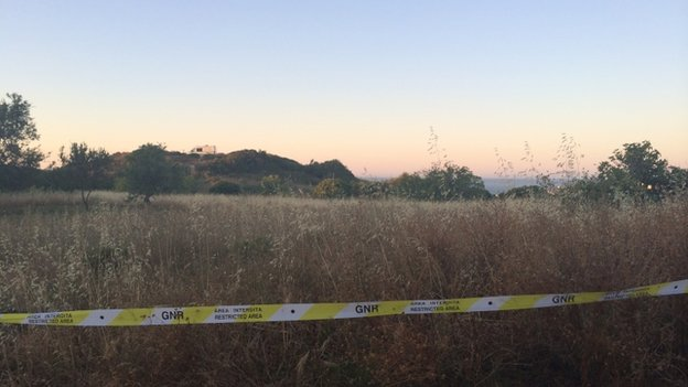 Police tape in front of an area of scrubland