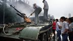 This archived photo shows Chinese residents checking an armoured personnel carrier which was set on fire by rioters on 4 June, 1989 near Tiananmen Square in Beijing