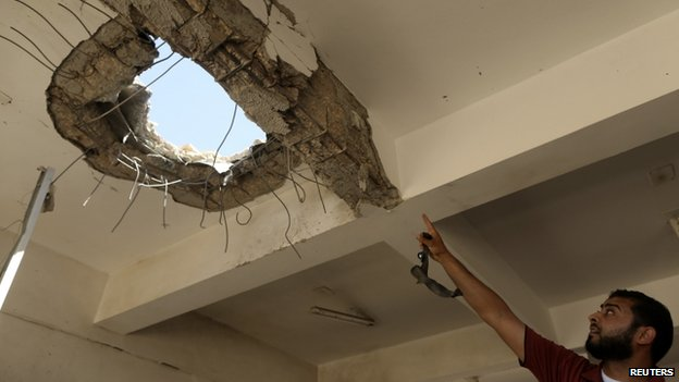 A teacher points to a hole in the ceiling after a building was bombed by a Libyan warplane at a university in Benghazi (1 June 2014)