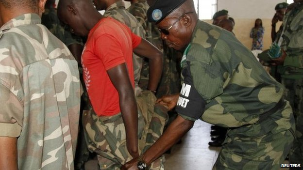 A Congolese soldier is stripped of his rank and uniform after the mass trial of 39 soldiers inside a military court in Goma in eastern Democratic Republic of Congo, on 5 May 2014