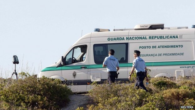 Two Portuguese police walking next to a parked police van