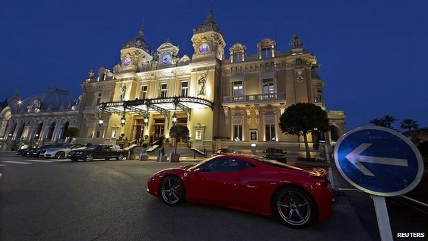 A luxury car is parked in front of the Casino de Monte Carlo in Monaco