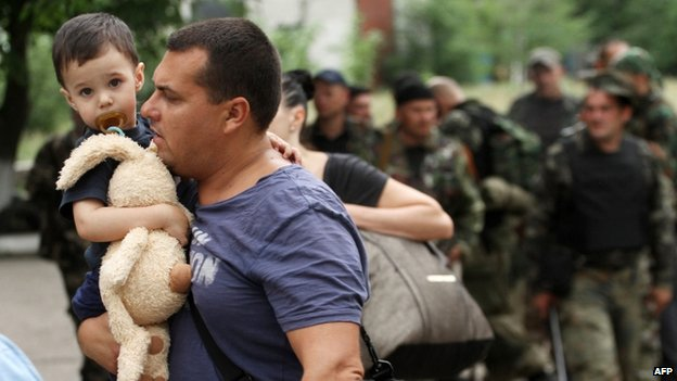 A man carries his son as he leaves his apartment during fighting in Luhansk. Photo: 2 June 2014
