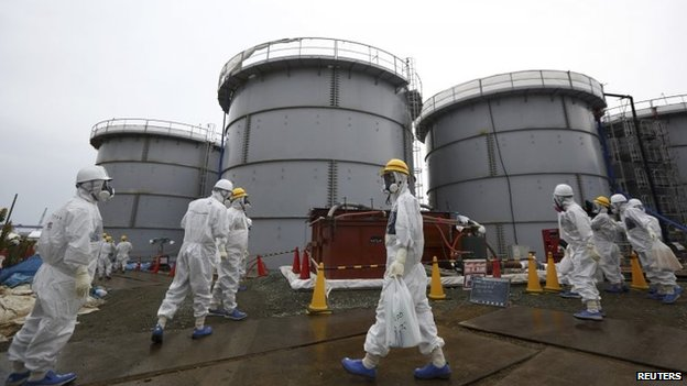 File photo: Journalists and Tepco employees wearing protective suits and masks walk past storage tanks for radioactive water at the tsunami-crippled Fukushima Daiichi nuclear power plant in Fukushima prefecture, Japan, 7 November 2013