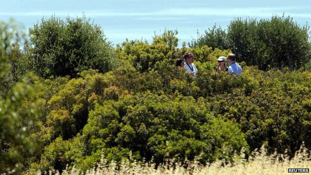 Police searching an area of scrubland in Praia da Luz