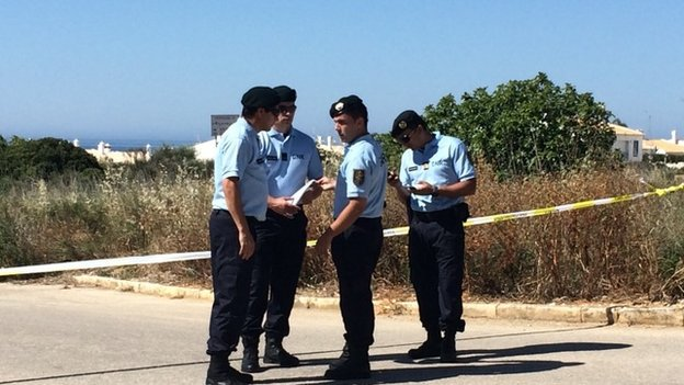 Officers standing outside the cordoned off section of scrubland