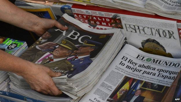 A woman arranges special editions of Spanish newspapers featuring a portrait of Spanish King Juan Carlos. Photo: 2 June 2014