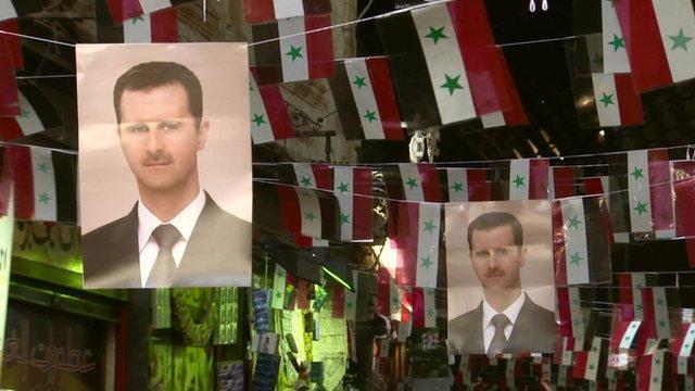 Pictures of Bashar al-Assad hanging amongst Syrian flags
