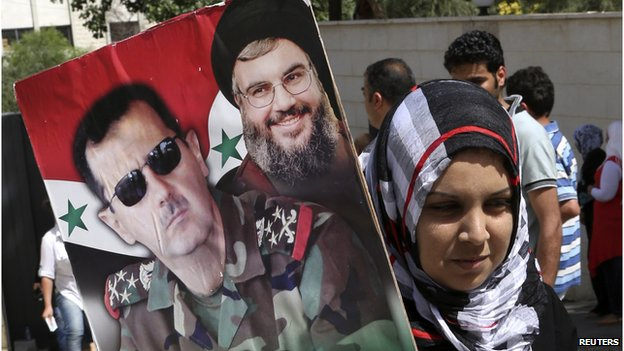 "A Syrian national living in Beirut holds a picture of Syria""s President Bashar al-Assad and Hezbollah leader Sayyed Hassan Nasrallah as they arrive to cast their votes ahead of the June 3 presidential election at the Syrian Embassy in Yarze, east of Beirut May 28"