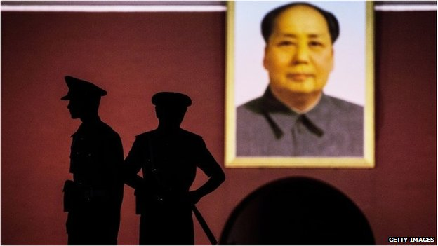 Chinese security officers stand under a portrait of the late Mao Zedong outside the Forbidden City at Tiananmen Square on June 2