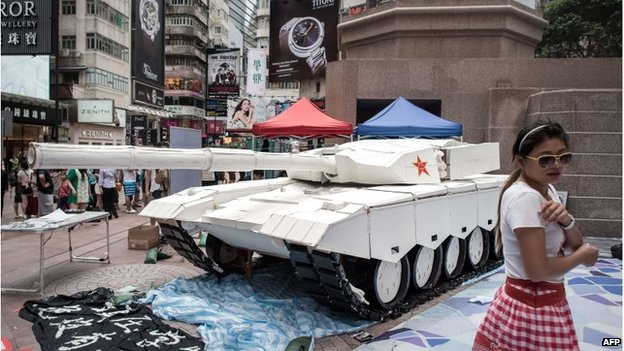 A woman poses next to a tank replica displayed to symbolise the Tiananmen military crackdown in Hong Kong on June 3