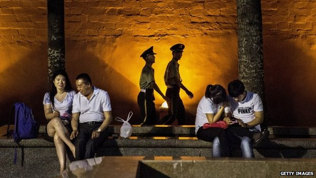 Chinese Paramilitary security force officers walk passed couples as they sit near Tiananmen Square on June 2