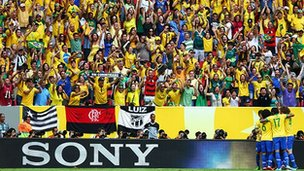 Brazil players celebrate in front of a Sony hoarding