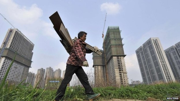 A garbage collector walks past residential and office buildings in construction, in Hefei, Anhui province, in this 3 April 2014 file photo
