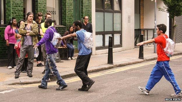 Actors cross a road