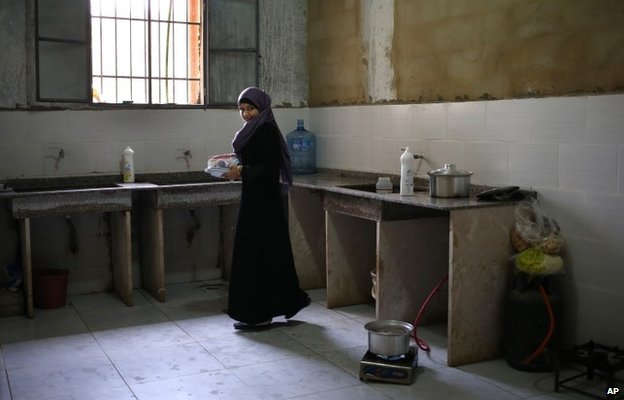 A Syrian woman carries plates in a kitchen at a centre for refugees in Kirbet Daoud, north Lebanon (29 May 2014)