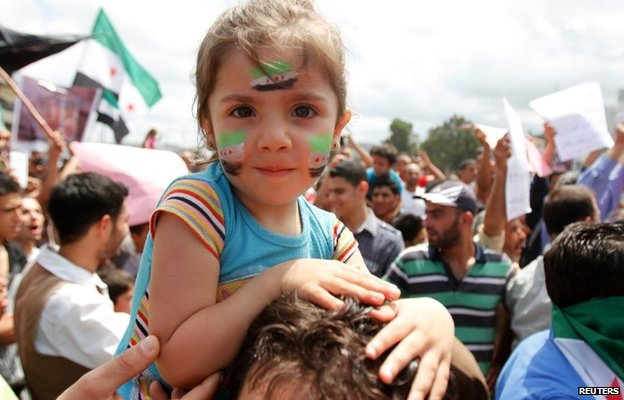A girl with Syrian opposition flags on her face at a protest against Bashar al-Assad in Tripoli (1 June 2014)