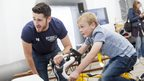 Boy trying out exercise bike challenge with a coach