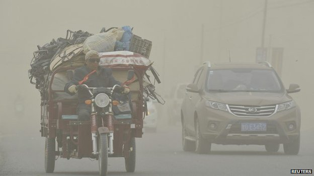 A motorcyclist rides past a car during a dust storm in Hami, Xinjiang Uygur Autonomous Region, 23 April 2014