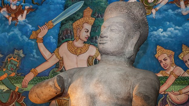 The Bhima statue is displayed in front of a painting representing the Angkor Wat bas-relief depicting the churning of the Sea of Milk during a ceremony to handover three statues back to Cambodia at the Council of Ministers on 3 June, 2014 in Phnom Penh, Cambodia