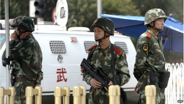 Armed Chinese police stand guard near Tiananmen Square in Beijing on June 4