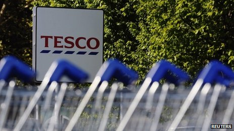 Shopping trolleys are seen lined up at a Tesco supermarket