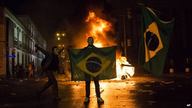 A demonstrator holds a Brazilian flag in front of a burning barricade during a protest in Rio de Janeiro on 17 June 2013
