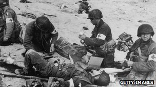 American medics administer first aid to wounded soldiers on Utah beach in Normandy, France, 6 June 1944