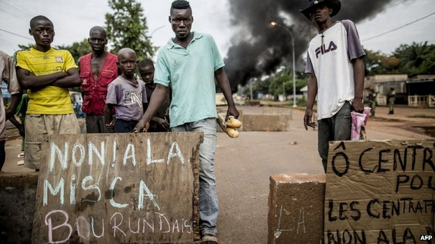 "People angered by an attack on a church in central Bangui hold a sign (L) reading ""No! To Burundian Misca [peacekeepers]"" as they protest near a barricade of burning tyres in the Bea-Rex district of Bangui on 29 May 29 2014"
