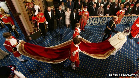 Three pageboys hold the train of the Queen's gown as she leaves