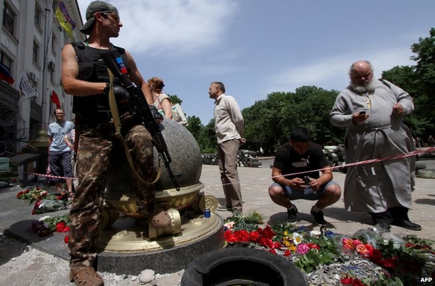 Flowers are laid at the scene of Monday's air attack in Luhansk, 4 June