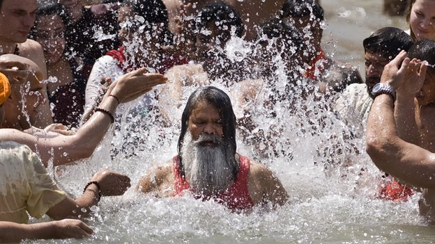 Hindu devotees splash water on a Hindu Sadhu during the Kumbh Mela festival in Haridwar