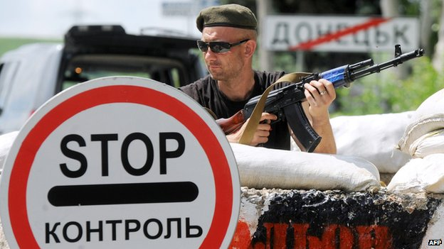 A pro-Russian militant guards a checkpoint on the road between Donetsk and Mariupol, near the eastern Ukrainian city of Donetsk on June 1