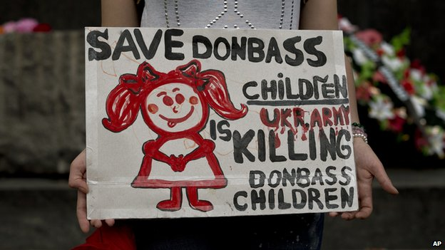 A woman holds a poster while attending a pro-Russian rally in Donetsk, Ukraine, Sunday, June 1