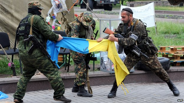 Pro-Russian fighters of Vostok (East) battalion rip apart an Ukrainian flag outside a regional state building in the eastern Ukrainian city of Donetsk on May 29