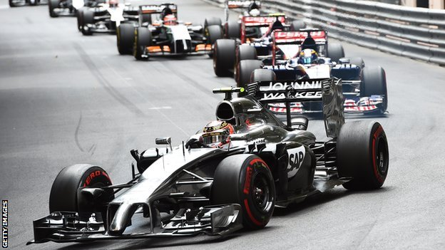 image of a row of formula one cars turning a corner