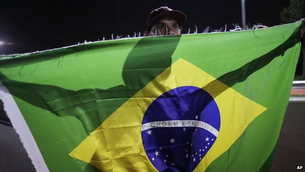 A member of the Homeless Workers Movement carries a Brazilian flag during a protest demanding better public services in Sao Paulo on 4 June, 2014