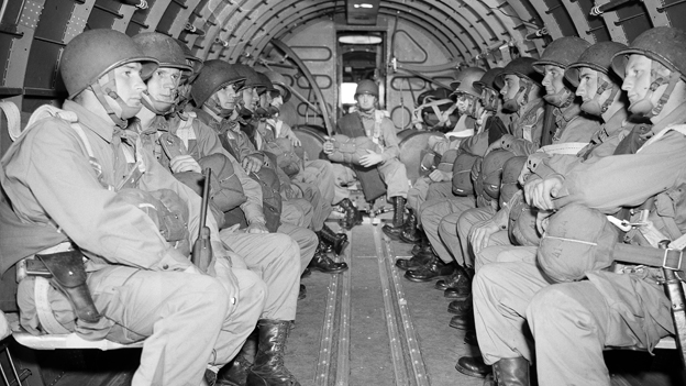 US paratroopers, heavily armed, sit inside a military plane as they soar over the English Channel en route to the Normandy French coast for the Allied D-Day invasion