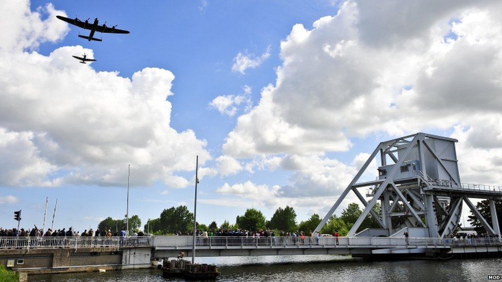 Spitfire and a Lancaster flying over Pegasus Bridge