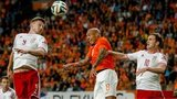 Nigel de Jong (C) of Netherlands vies with Wales players Simon Church (L) and Andy King