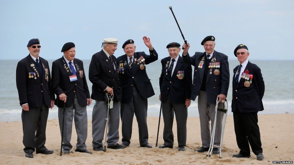 Seven British veterans standing on a beach in France