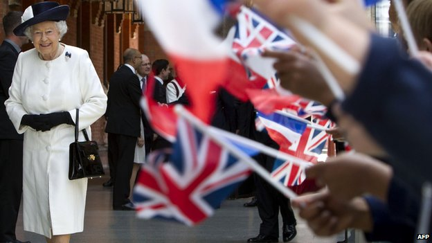 School children waving union jacks as the Queen walks past
